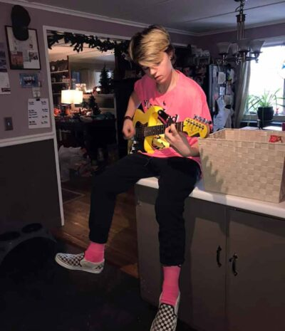 A boy wearing a bright pink shirt with matching pink socks is sitting on a kitchen counter playing a guitar