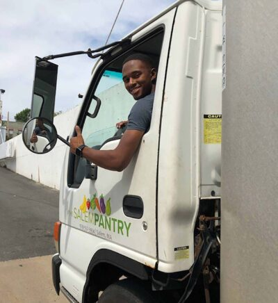 A man smiling driving s Salem Pantry food truck