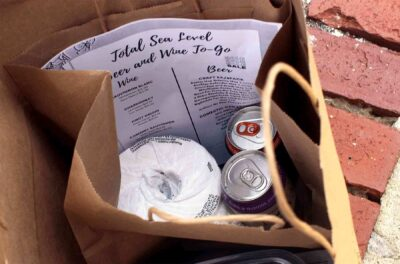 Sea Level Oyster Bar beer menu, toilet paper roll  and beer cans in a paper grocery bag
