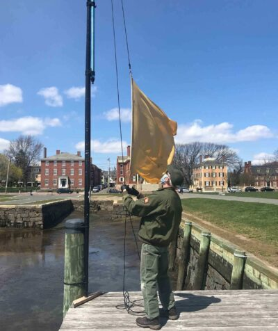 John Newman from Salem Maritime National Historic Site, takes down the quarantine flag before a storm.