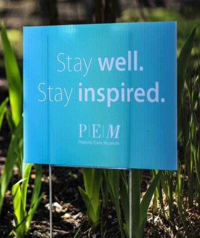 "A blue printed banner sign that says ""Stay well. Stay inspired"" stands in green grass."