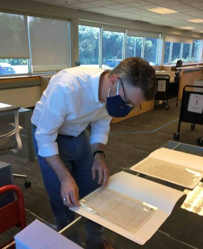 Phillips Library Head Librarian Dan Lipcan examines Salem witch trial documents in the Collection Center in Rowley. Photo by Reference Assistant Amanda Fowler.