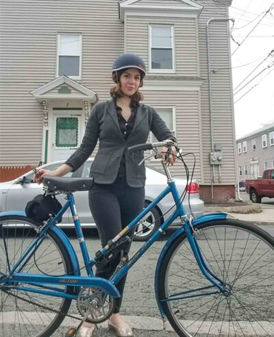 A woman stands behind a bicycle with a beige house in the background. The author and her beloved 1972 Raleigh.