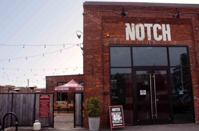 Notch Brewing brick building with Notch sign above door. To the leftof the building a patio area with tables and umbrellas