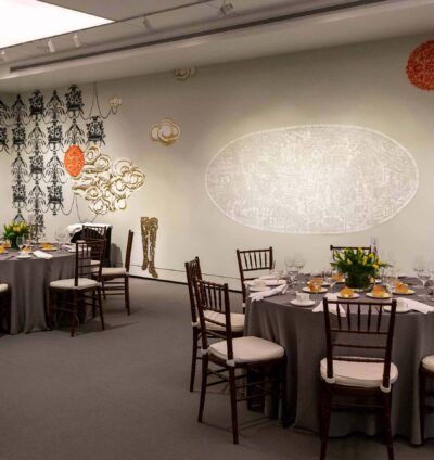 Round tables and chairs set for a wedding reception in a room with stenciled artwork on white walls