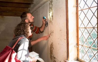 Two people inspecting a wall in the John Ward House