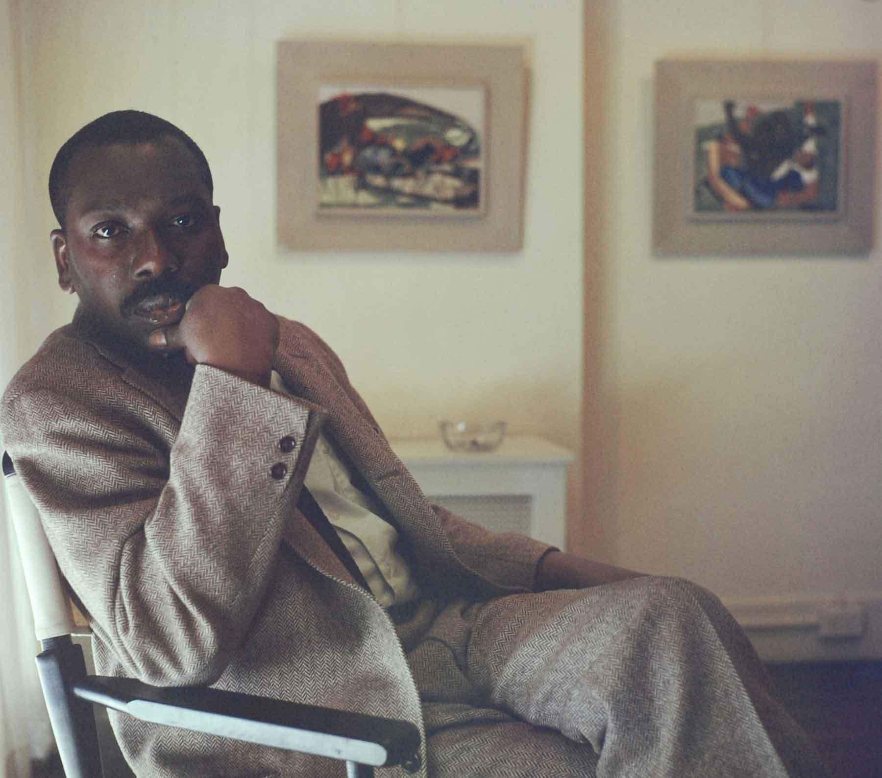 Jacob Lawrence seated in front of Struggle panels 26 and 27, 1958. © Robert W. Kelley/The LIFE Picture Collection/Getty Images.