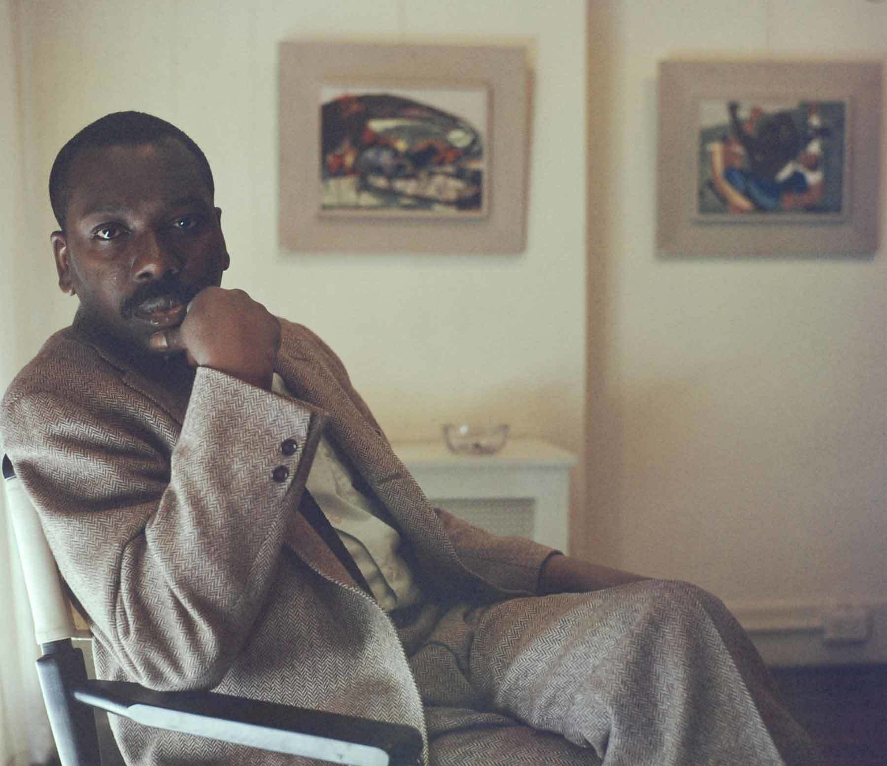Jacob Lawrence seated in front of Struggle panels 26 and 27