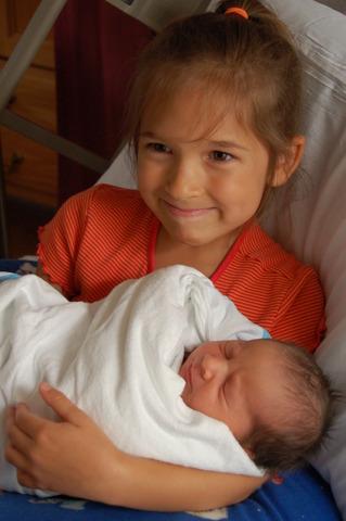 Elaina holds her new sister.