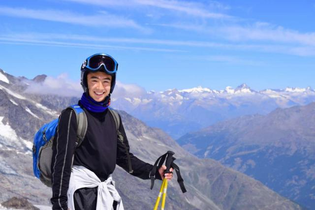 Teenage traveler summer skiing in Swiss Alps Switzerland