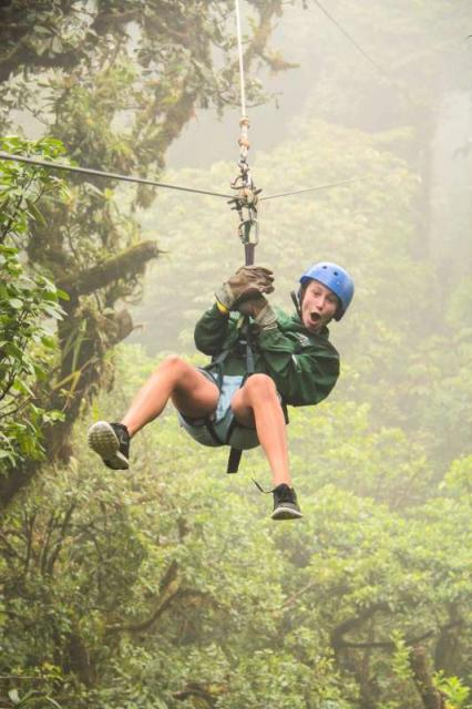 Teen boy zip-lines through the jungle on summer adventure program in Costa Rica.