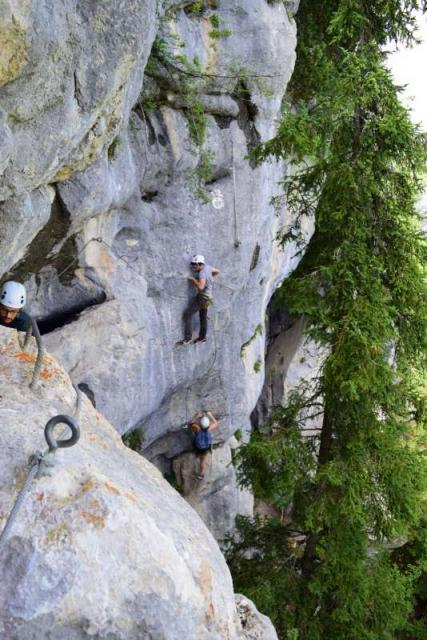 Happy teens rock climbing in Europe on adventure trip