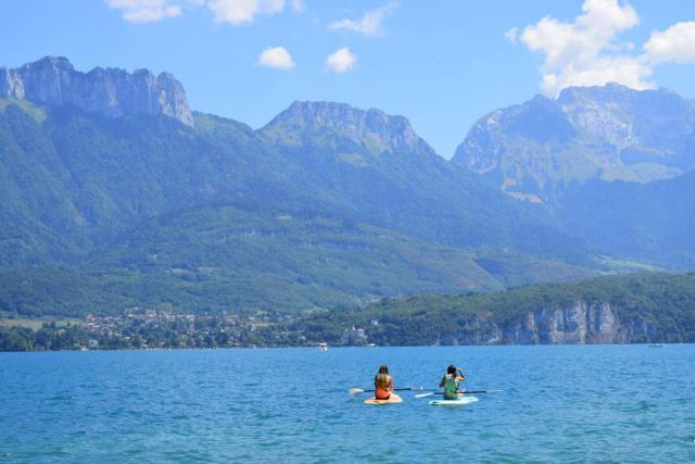 Teen travelers doing water sports in Alps on summer adventure tour
