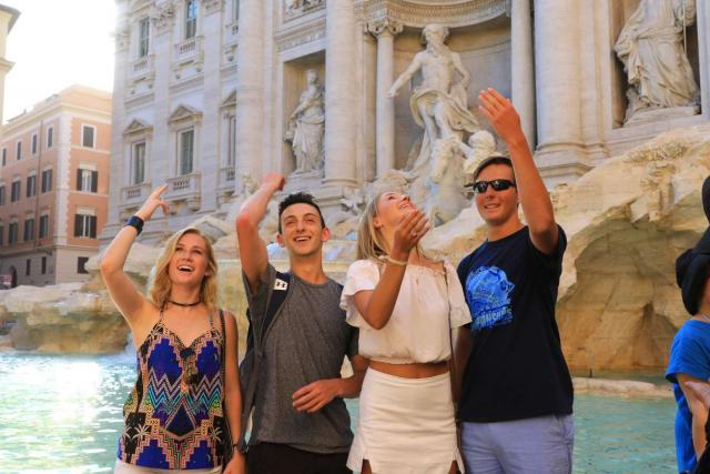 Teenage travelers throw coin in Trevi fountain during summer youth travel program in Rome