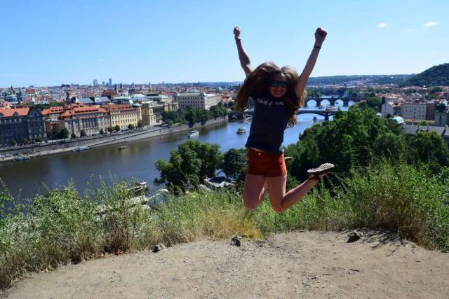 Teen traveler jumping in Prague on summer adventure travel program