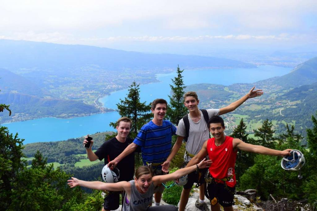 Group of happy teens on mountaintop during summer adventure program