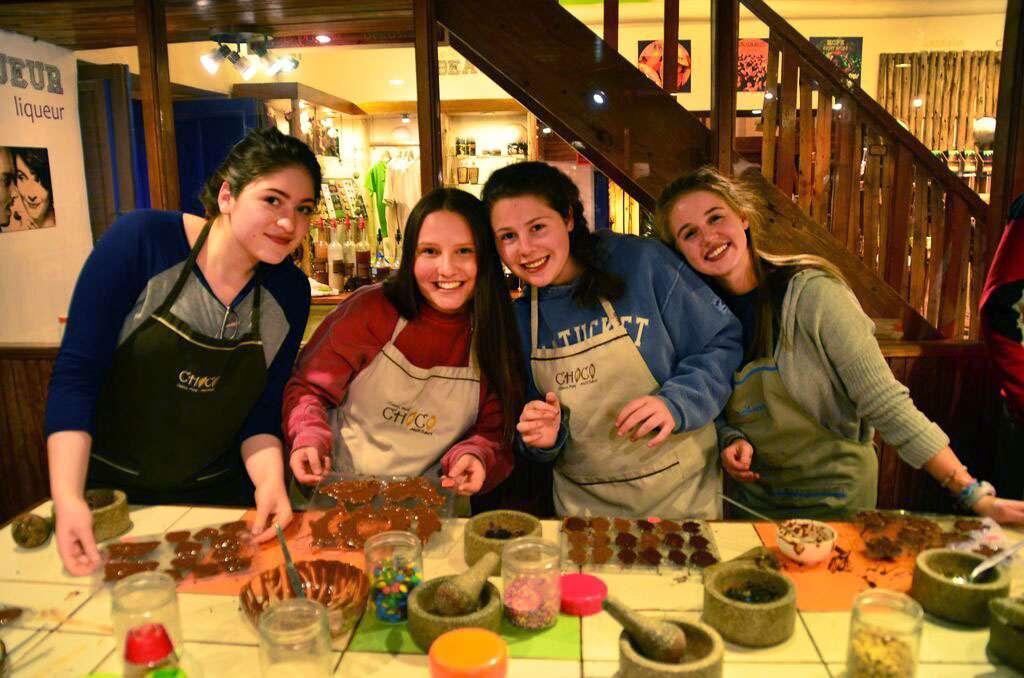 Things to do in Peru for teens. Group of teen girls cook a meal together during their summer trip to Peru.