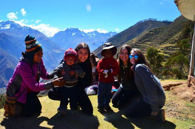 A group of students pose with local children on their teen tour of Peru.