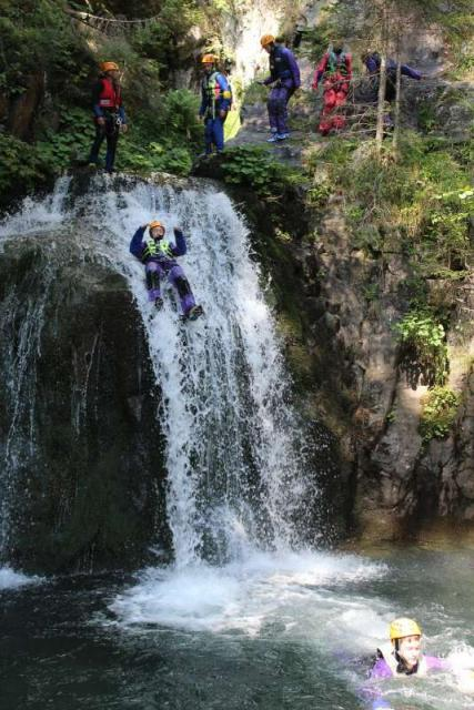 Teen traveler canyoning in Lake Bled on summer adventure travel program