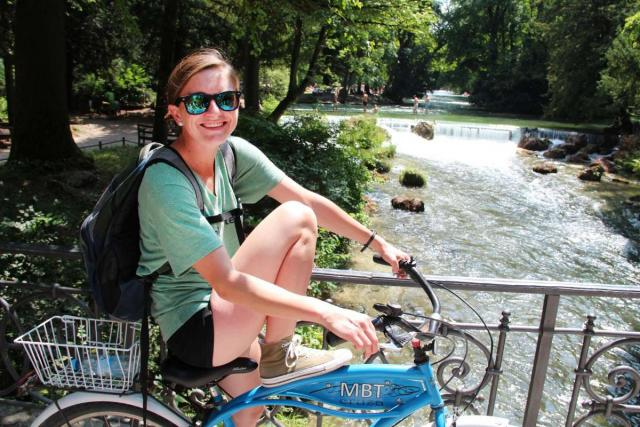 Teen traveler biking by waterfall on youth summer travel program