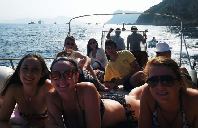 Teens smile on their private boat cruise along the Amalfi Coast on their summer tour in Italy.