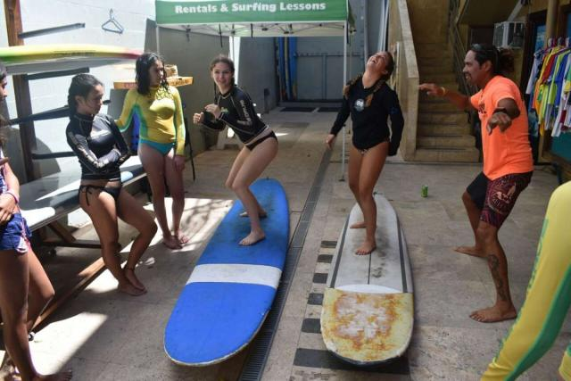 Teens learn how to surf before hitting the water in Hawaii on summer travel program.