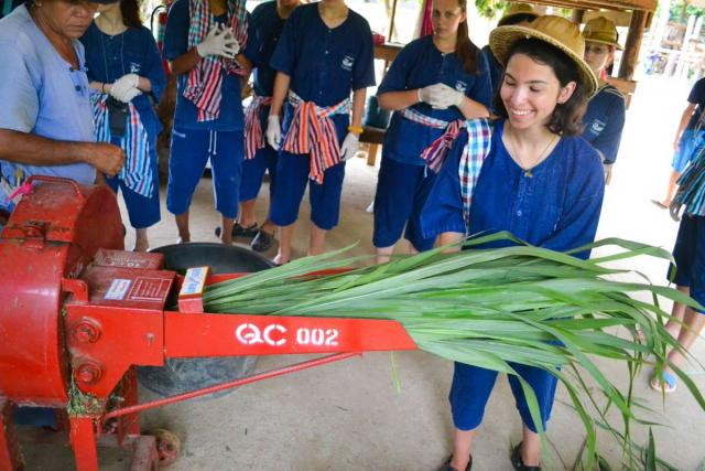 Teenage travelers make sugarcane juice during summer youth travel program in Thailand