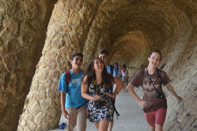 Happy teenage travelers in Barcelona's Parc Guell on summer youth adventure program