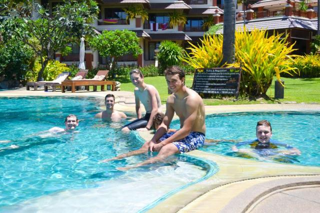 Teenage travelers swim in hotel pool during summer youth travel program in Thailand