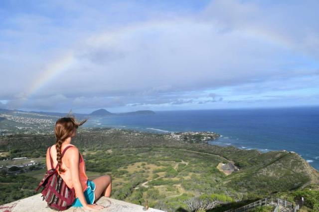 Teen girl admires rainbow on summer service program in Hawaii.