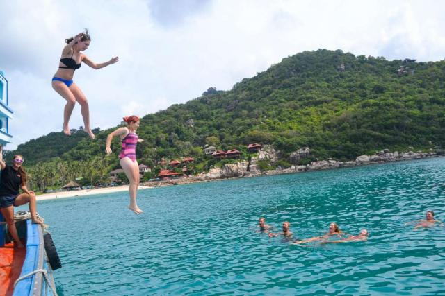 Teenage travelers jump into clear water during summer youth travel program in Thailand