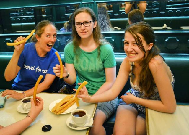 Teenage travelers eat churros and chocolate in Madrid on summer Spanish language immersion program