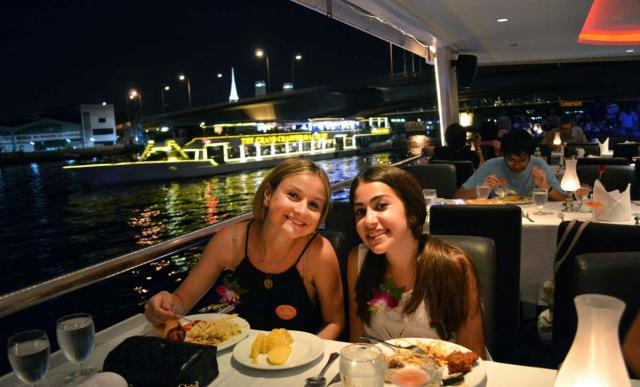 Teenage travelers enjoy local cuisine on riverboat cruise during summer youth travel program in Thailand