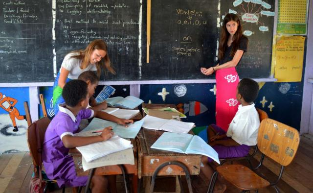 Teenage travelers teach Fijian children in school during summer youth program in Fiji