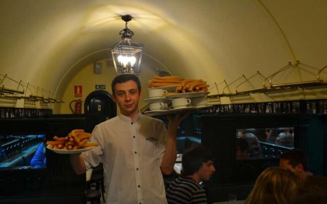 Waiter at churreria San Gines in Madrid carries churros and chocolate to teens on summer youth travel program