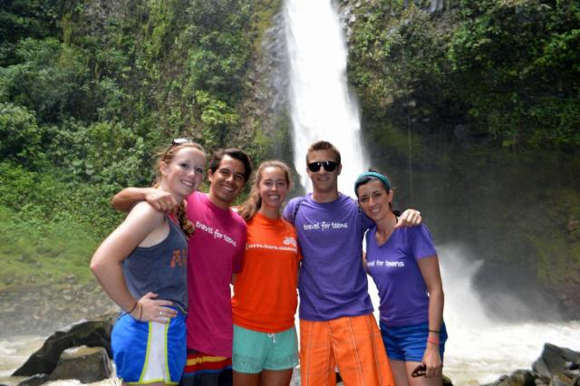 Teen group poses in front of a waterfall in Costa Rica on their summer adventure tour.