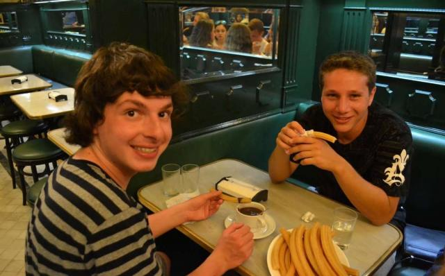 Teenage travelers eat churros and chocolate in Madrid on summer youth travel program