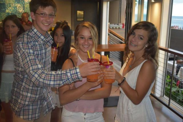 Teens enjoy fresh juice on their summer travel camp tour of Hawaii.