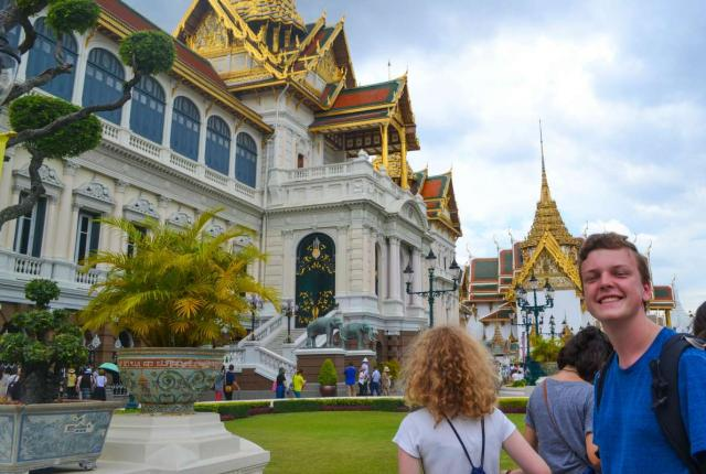 Teen traveler visits temple during summer youth travel program in Thailand