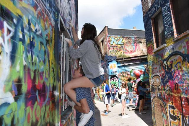Teen travelers on street art tour in Europe during summer travel program
