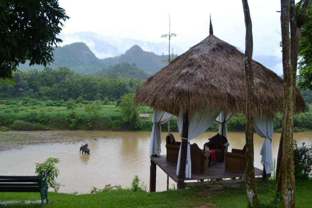 View of thatched roof hut and river seen by teenage travelers during summer youth program in Southeast Asia