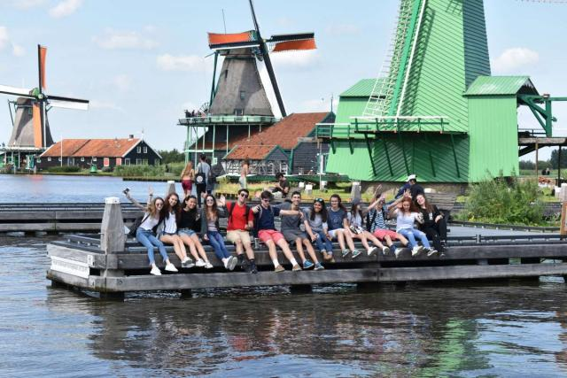 Teenage travelers in traditional Dutch village on summer youth trip to Netherlands