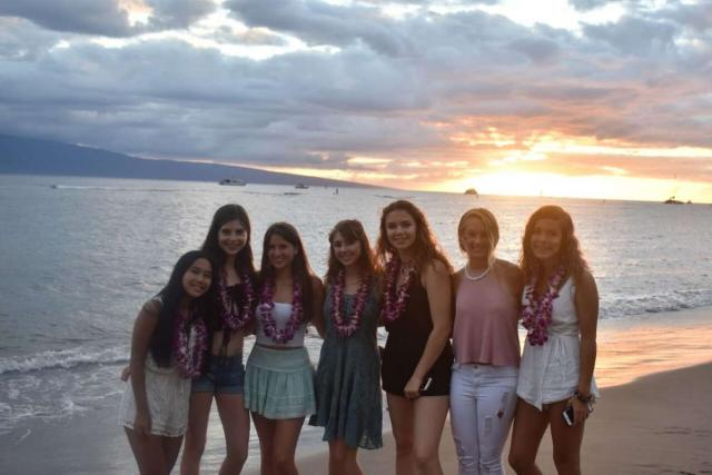 Students enjoy the sunset on a beach in Hawaii on summer teen service program.