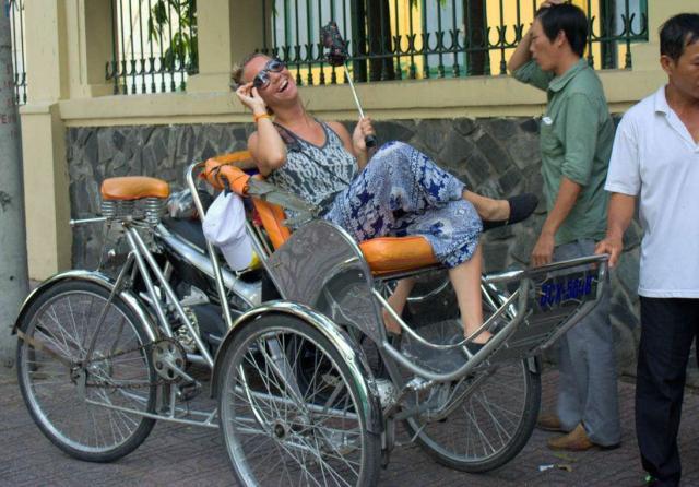 Teenage traveler having fun on rickshaw tour during summer youth travel program in Southeast Asia