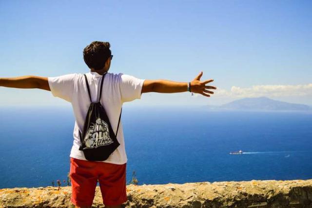 Teenage boy traveler admires views of Mediterranean Sea during summer youth travel program in Greece