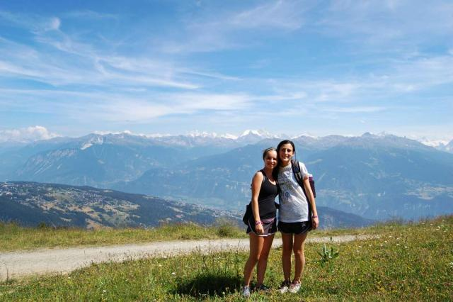 Teenage travelers hike through Swiss Alps on summer youth adventure travel program