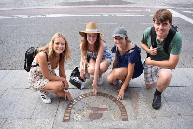Teen travelers at Madrid Kilometer 0 in Puerta del Sol during summer Spanish language immersion program