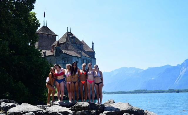 Teens relax at Swiss lake with chateau during summer adventure travel program