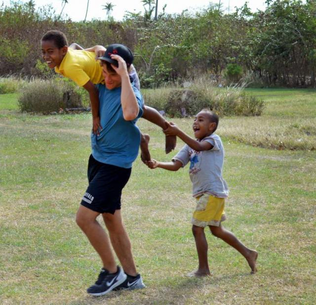 Teenage American traveler plays with local Fijian boys during summer youth program in Fiji