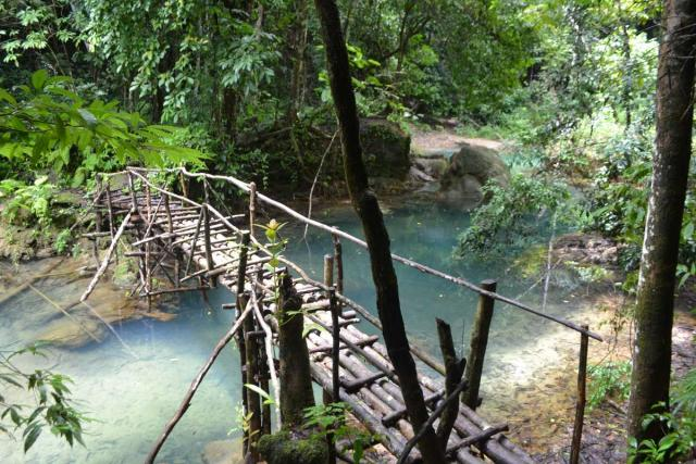 Wooden bridge over river seen by teenage travelers during summer youth program in Southeast Asia